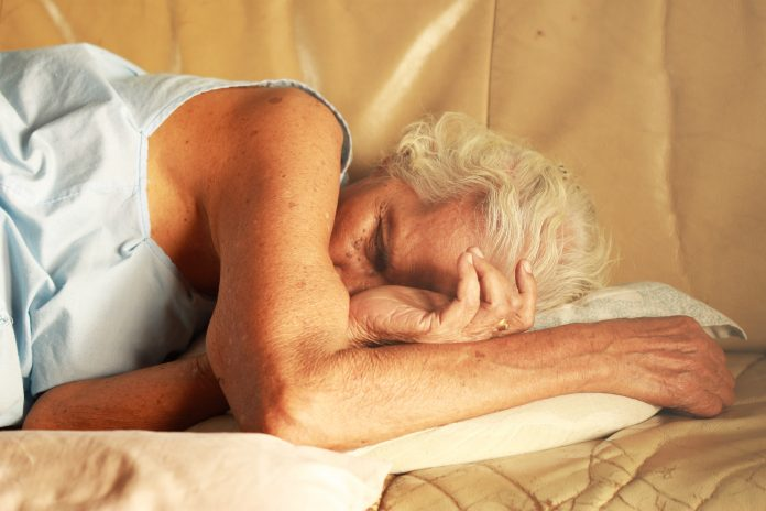 old grey haired woman sleeping on bed scaled