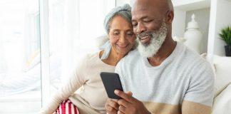happy diverse senior couple using smartphone home shutterstock 1448949023 AM CL